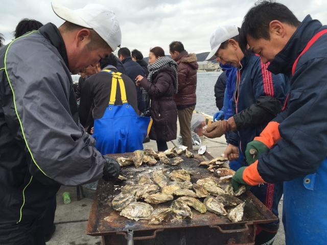 牡蠣を剥く漁師たち。ナイフ使いには高度な技がいる